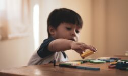 Barn leger med legetøj på bord