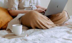Dame skriver på sin pc i sin seng